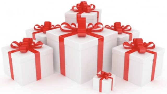 Beautifully arranged Christmas gifts in white boxes with red ribbon and red bows.